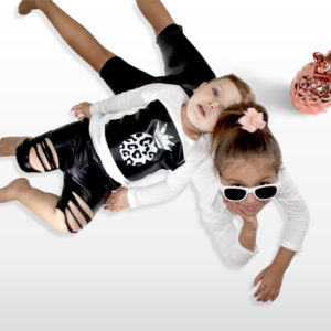 La Vera Kids - Little Rebels Collection - Lifestyle Image - Kids ripped leatherette pants shorts and pineapple print white long sleeve top with flower hairclip
